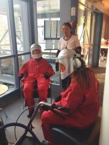 Typische Situation in der Altenpflege. Bewohner sitzen in Gruppen. Hier Pflegekräfte mit dem Altersanzug AgeExplorer.