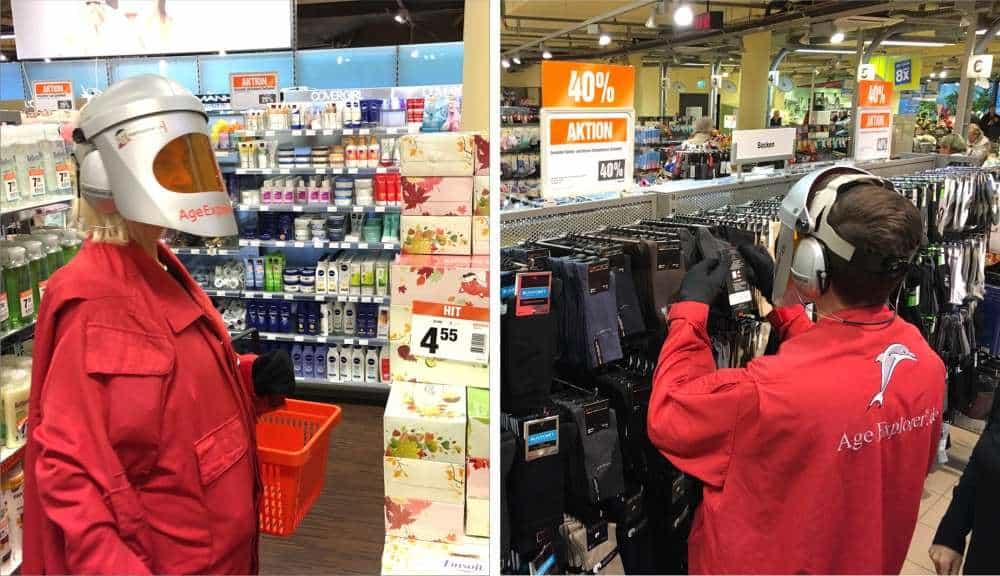 Zwei Handelsmanager analysieren im Altersanzug AgeExplorer einen Shop aus dem Blickwinkel alter Kunden.